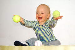 Happy baby plays with tennis balls Royalty Free Stock Image