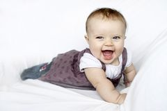 Happy baby portrait with blue eyes. Cute infant child with blue eyes standing on the white couch and laughing stock photography