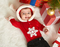 Happy baby portrait in christmas decoration, lie on fur near fir tree and gifts, winter holiday concept Stock Photos