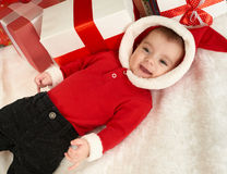 Happy baby portrait in christmas decoration, lie on fur near fir tree and gifts, winter holiday concept Stock Image
