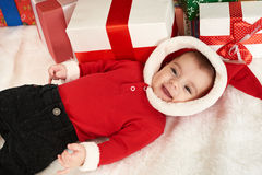 Happy baby portrait in christmas decoration, lie on fur near fir tree and gifts, winter holiday concept Royalty Free Stock Photos