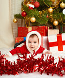Happy baby portrait in christmas decoration, lie on fur near fir tree and gifts, winter holiday concept Stock Photo