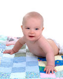 Happy Baby on Quilt. Cute baby lying in front of white background on a multicolored quilt Stock Photography
