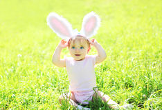 Happy baby with rabbit ears sitting on grass in sunny summer Stock Images