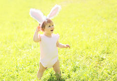 Happy baby with rabbit ears in sunny summer Stock Photos