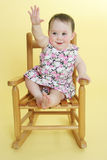 Happy baby raising hand. Sitting in wooden rooking chair Royalty Free Stock Image