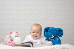 Happy baby reading a book. Smiling baby girl reading a book with little toy friends Stock Photo