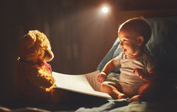 Happy baby reading a book with teddy bear in bed. In the dark Stock Photos