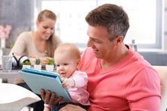 Happy baby reading e-book royalty free stock photos