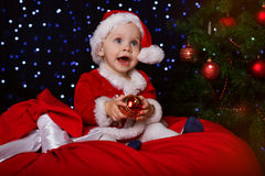 Happy baby with red Christmas ball near fir-tree Stock Image