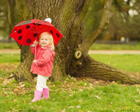 Happy baby with red umbrella outdoors Royalty Free Stock Images