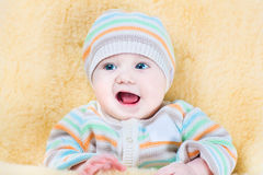 Happy baby relaxing in sheepskin stroller foot muff Royalty Free Stock Images