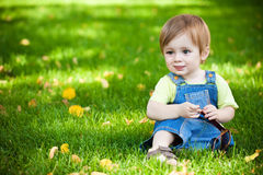 Happy baby resting on the green grass. picnic Stock Photos