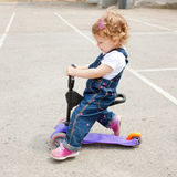 Happy baby riding on a scooter Stock Image