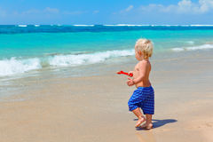 Happy baby run to ocean surf on family beach vacation Stock Photos