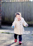 Happy baby running in the street. Happy baby girl with cheeky smile running in the street Royalty Free Stock Photos