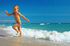 Happy baby running from surf on the beach Royalty Free Stock Photography