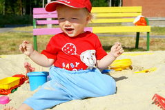 The happy baby in a sandbox. The little boy sits on sand in a court yard  in the summer and plays having opened a mouth Royalty Free Stock Photography