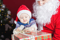 Happy baby and Santa Claus with big gift, present box Stock Photos
