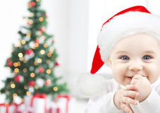 Happy baby in santa hat over christmas tree lights Stock Image