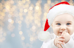 Happy baby in santa hat over holidays lights Royalty Free Stock Image