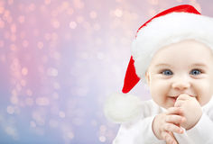 Happy baby in santa hat over holidays lights Stock Image