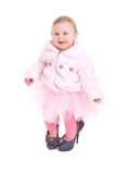 Happy baby in the shoes of adults. And a pink tutu on the white backgraund Royalty Free Stock Photo