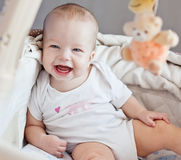 Happy baby sitting in bed Royalty Free Stock Photos