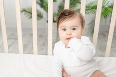 Happy baby sitting in the crib in a white bodysuit and sucking his finger