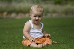 Happy baby sitting on grass. Happy baby, sitting on grass wearing white vest and orange shorts Stock Photos