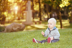 Happy baby sitting in the green grass Royalty Free Stock Photos