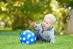 Happy baby sitting in the green grass Stock Images