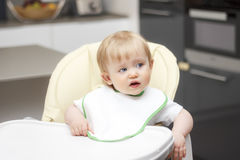 Happy baby sitting in highchair and eating porridge. Baby learning to eat Royalty Free Stock Photography