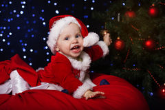 Happy baby is sitting near Christmas fir-tree Stock Photos