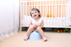 Happy baby sitting on potty. Baby boy sitting on potty in home Royalty Free Stock Photos