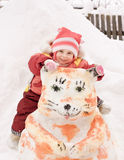 Happy baby sitting on a snowman Royalty Free Stock Photo