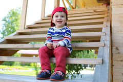 Happy baby sitting on stairs outdoors Stock Images