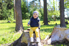Happy baby sitting on stub in forest Stock Images