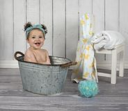 Smiling infant girl in bubble bath. Happy baby sitting in tiny metal bath tub with towel and robe Royalty Free Stock Photos