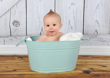 Happy baby sitting in washtub Stock Photo