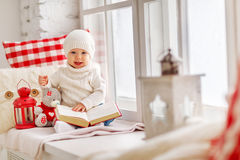 Happy baby sitting on window of house in winter Stock Photos