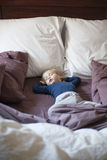 Happy baby sleeping between cushions. Portrait of happy blonde caucasian baby nineteen month age with blue shirt sleeping in brown sheets bed between cushions stock photography