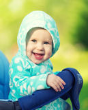 Happy baby smiling in a blue hood in the stroller for a walk in Stock Photography