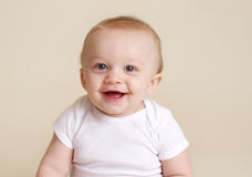 Happy Baby Smiling and Laughing. Happy baby sitting, milestones and development concept Royalty Free Stock Photos