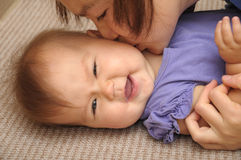 Happy baby smiling playing with mother Stock Photos