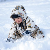 Happy baby in snow. Portrait of a happy baby child, boy or girl,  in snow suit playing in a fresh snow Royalty Free Stock Photo