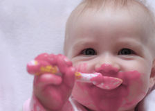 Happy baby with a spoon in the mouth Royalty Free Stock Photo