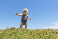 Happy baby spreads her arms welcoming Royalty Free Stock Photography