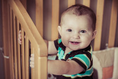 Happy baby standing up in his crib Royalty Free Stock Images