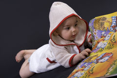 Happy baby on story time. Curious happy baby on black surface reading a story Royalty Free Stock Image